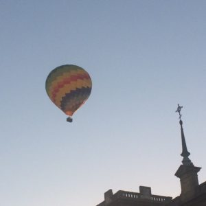 Hot air ballon cruising over the city in the sunrise